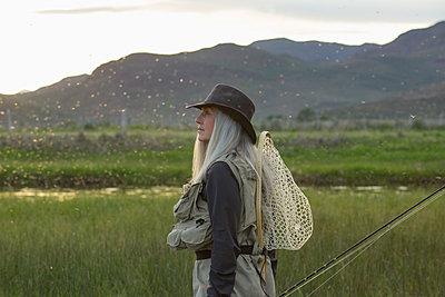 Caucasian woman wearing fishing gear in remote lake - p555m1408482 by Steve Smith