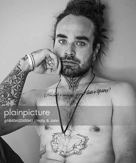 Young man with bare chest and lots of tattoos - p1640m2245941 by Holly & John