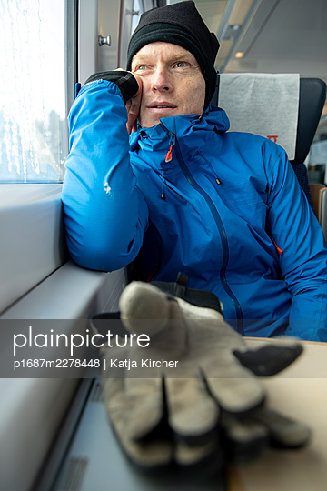 Man sitting on train looking out of the window - p1687m2278448 by Katja Kircher