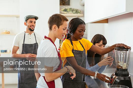 Friends and instructor in a cooking workshop using blender - p300m1586953 von Bonninstudio