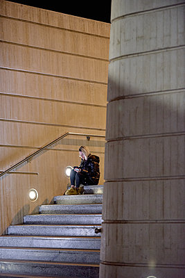 Trendy girl sitting on the stairs looking at her smartphone - p1166m2096561 by Cavan Images