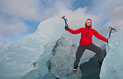woman climbing iceberg on the south coast of Iceland using ice pick - p1166m2269503 by Cavan Images