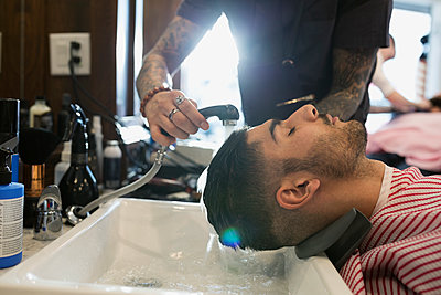 Barber washing man - p1192m1128061f by Hero Images