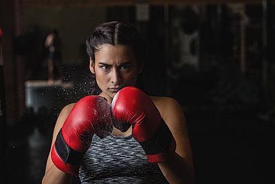 Portrait of woman in boxing gloves - p1315m1199037 by Wavebreak