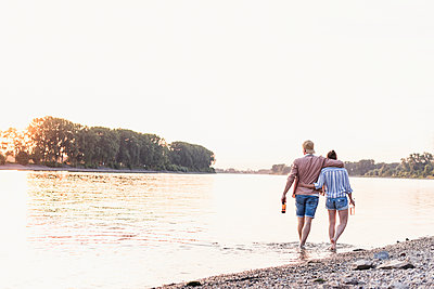 Young couple wading in river at sunset - p300m2023829 by Uwe Umstätter