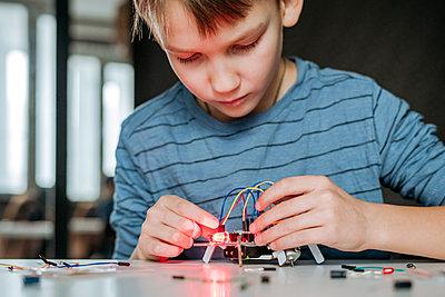 Boy assembling robot at home - p300m2170133 by Ekaterina Yakunina