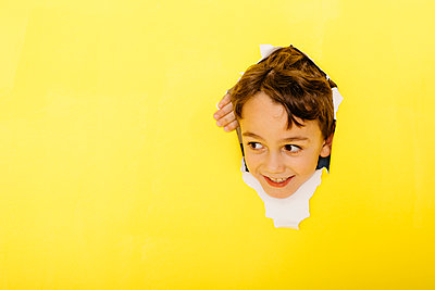 Smiling cute boy tearing yellow paper while looking away - p300m2198452 by Josep Rovirosa