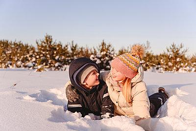 Playful siblings lying on snow against sky during winter - p300m2266006 by Ekaterina Yakunina