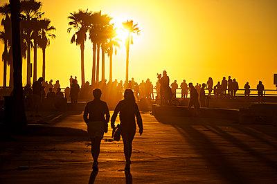 People walk toward the Venice Skate Park as the sun sets over Venice Beach, California. - p343m1089897 by David Zentz