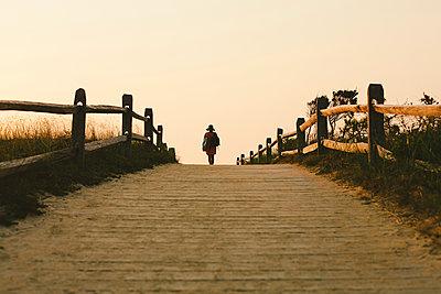 Silhouette of woman walking on wooden walkway - p555m1409672 by Shestock