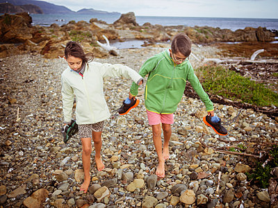 Mixed race brother and sister carrying their shoes on rocky beach - p555m1414863 by Donald Iain Smith