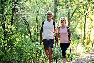 Smiling mature couple hiking together in forest - p623m2271770 by Frederic Cirou