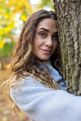 Young woman embracing tree - p975m2222458 by Hayden Verry