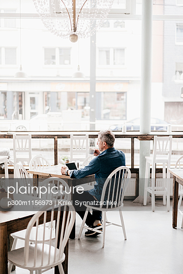 Mature man with digital tablet drinking coffee in cafe - p300m1156973 by Kniel Synnatzschke