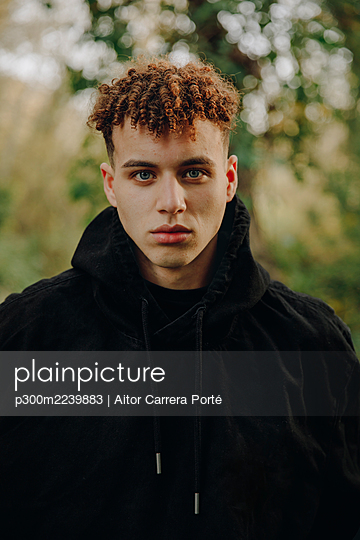 Young man wearing hooded shirt staring while standing at park - p300m2239883 by Aitor Carrera Porté