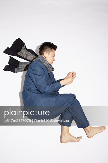 Asian man in pyjama and scarf against white background - p817m2179078 by Daniel K Schweitzer