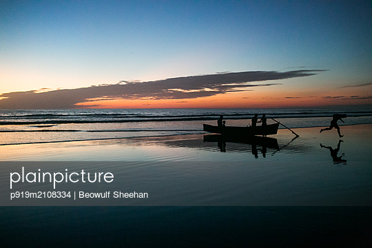 Fishermen return with fishing boat to beach at sunset - p919m2108334 by Beowulf Sheehan