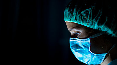 Portrait of young female surgeon, wearing mask and a surgical mask, in front of black background - p1166m2190765 by Cavan Images