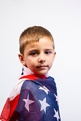 Beautiful portrait of a 4-year-old blond boy wrapped in the American flag - p1166m2193951 by Cavan Images