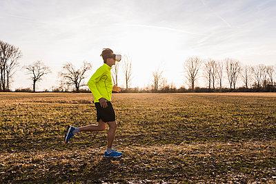 Man wearing VR glasses running in rural landscape - p300m1356529 by Uwe Umstätter