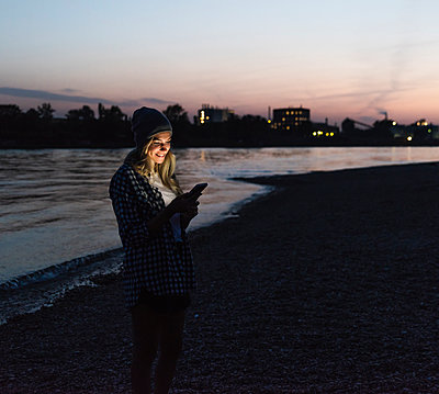 Young woman using smartphone on riverside in the evening - p300m2004243 by Uwe Umstätter
