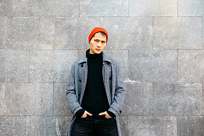 Portrait of stylish young man wearing cap, black turtleneck pullover and grey coat - p300m2080573 by Josep Rovirosa