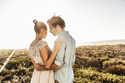 Affectionate young couple embracing at the coast in summer - p300m2167506 by Floco Images