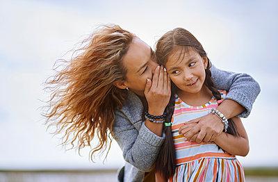 Mother whispering secret in daughter's ear - p300m2273748 by Arman Zhenikeyev