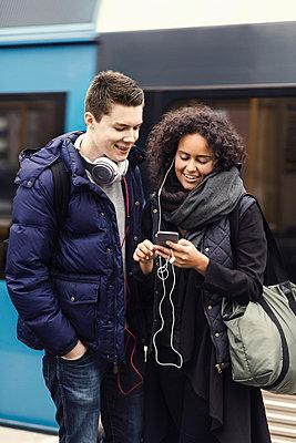 Multi-ethnic couple listening music through mobile phone on subway platform - p426m1003761f by Maskot