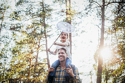 Smiling father carrying happy daughter on shoulder while walking in forest - p426m2212141 by Maskot