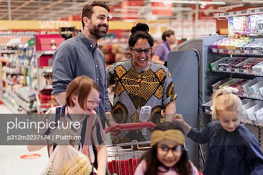 Family doing shopping in supermarket - p312m2237174 by Plattform