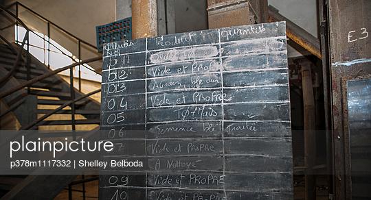 Chalk board schedule in abandoned grain store. France - p378m1117332 by Shelley Belboda