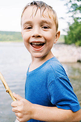 A drenched and smiling boy at the lake - p1166m2201458 by Cavan Images