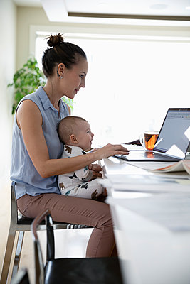 Mother with baby working from home, using laptop in kitchen - p1192m2088295 by Hero Images