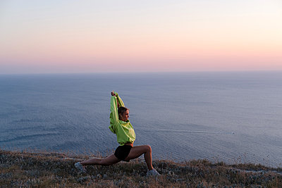 Athletic young woman is stretching and training on mountain near sea - p1363m2013488 by Valery Skurydin