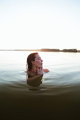 Frau genießt Bad im See - p1396m2039225 von Hartmann + Beese