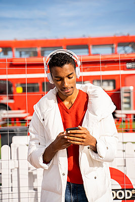 Young man headphones and smartphone outdoors - p300m2154497 by VITTA GALLERY