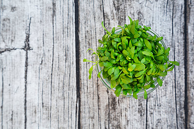 Glass of garden cress on grey wooden table, view from above - p300m926529f by Larissa Veronesi