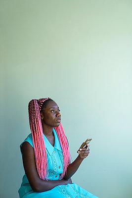 Junge Afrikanerin mit Dreadlocks benutzt Smartphone - p427m2089601 von Ralf Mohr