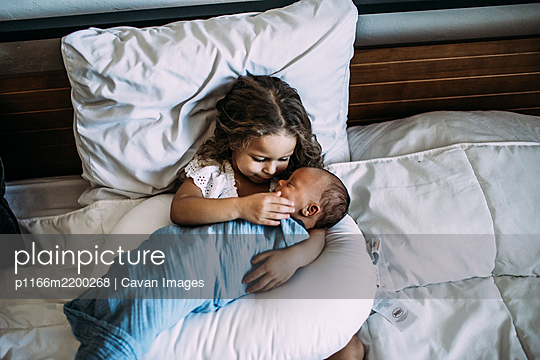 young girl holding newborn baby brother on bed - p1166m2200268 by Cavan Images