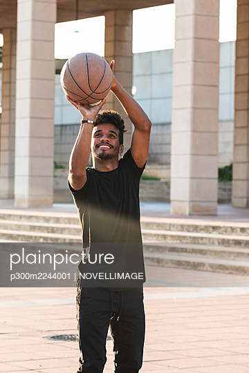 Smiling young man playing basketball in park during sunset - p300m2244001 by NOVELLIMAGE