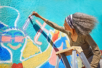 Senior woman painting vibrant mural on sunny wall - p1023m2066856 by Trevor Adeline
