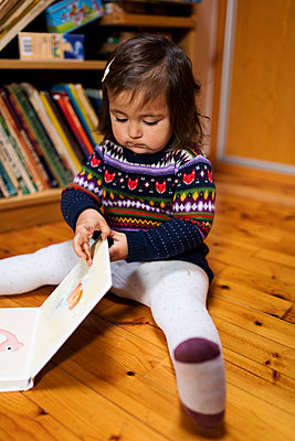 Toddler sitting on the floor reading a book - p1166m2094907 by Cavan Images