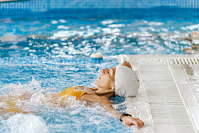 Beautiful woman wearing a swimming cap relaxing in a swimming pool - p1166m2189714 by Cavan Images