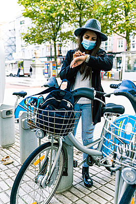 Young woman with mask chooses bicycle at a public rental point - p1166m2218419 by Cavan Images