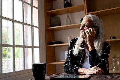 Senior woman talking on smart phone at home - p300m2287371 by Eloisa Ramos