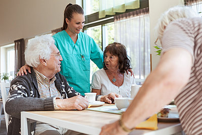 Smiling nurse listening to conversation of senior couple during breakfast at nursing home - p426m2072540 by Kentaroo Tryman