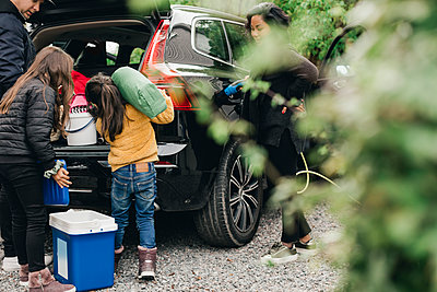 Family loading luggage in trunk while woman charging electric car - p426m2194971 by Maskot