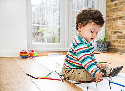 Male toddler sitting on floor drawing on long paper - p429m1418478 by Bonfanti Diego