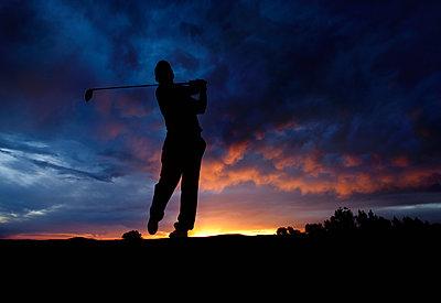 Caucasian golfer swinging golf club at sunset - p555m1478153 by Mike Kemp